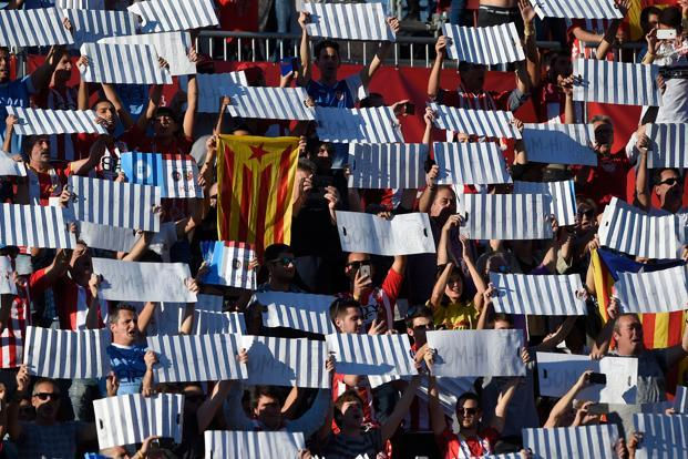 A Girona fan holds a pro-independence Catalan flag as others hold up placards to form a mosaic before their match against Real Madrid on Sunday. Photo: AFP
