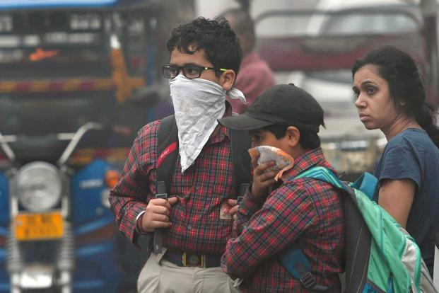Students using handkerchiefs to cover their face as smog covers the capital's skyline on Wednesday. Photo: PTI