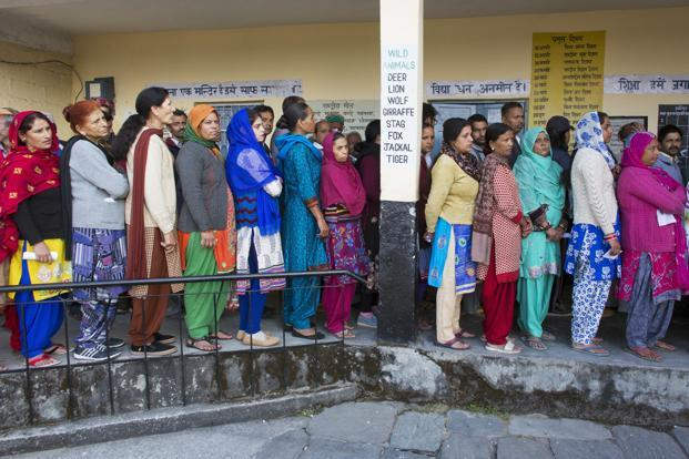 People stand in a queue to cast their votes at a polling station in Dharmsala on Thursday. Photo: AP