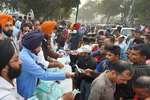 Volunteers handed out thousands of green surgical masks in New Delhi on Wednesday. Photo: PTI