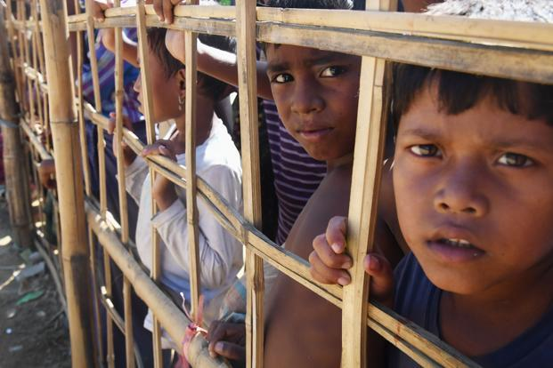 Young Rohingya refugees react as they look through a temporary bamboo barricade in Bangladesh's Ukhia district. Photo: Dibyangshu Sarkar/AFP
