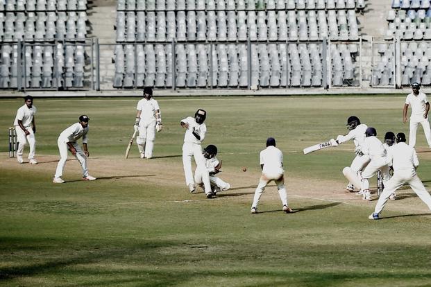 Baroda fielders close in near Mumbai's Dhawal Kulkarni during the final day  of the Ranji Trophy