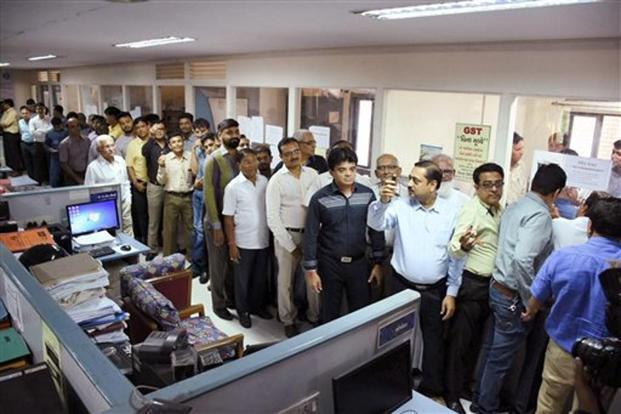 Merchants stand in queue at the I-T department with their account data to protest against slow systems in filing GST returns, in Surat on 6 November. Photo: PTI