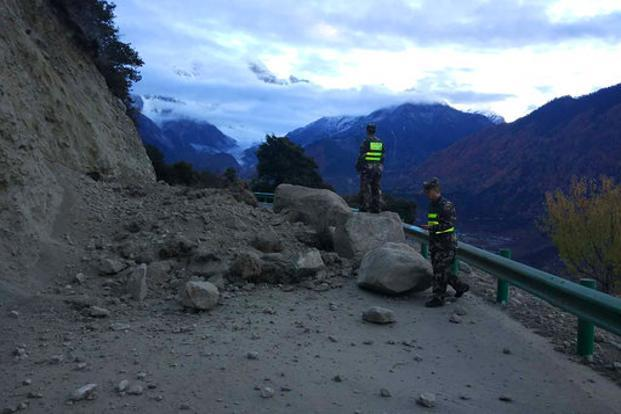 Rescuers look at a road blocked by fallen rocks in Paizhen town in Mainling of Nyingchi in Tibet on 18 November 2017 after a strong earthquake shakes the region. Photo: AP/Xinhua