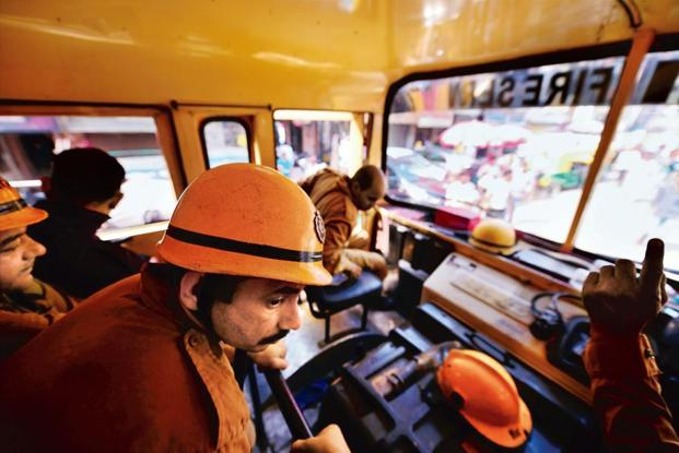 Firemen in a fire tender that is en route to Old Delhi, responding to a call reporting a gas leak. Photo: Pradeep Gaur/MInt