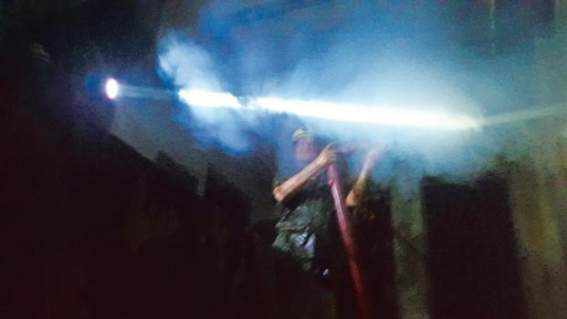 A firefighter is engulfed in steam and smoke as he trains the water hose on the flames inside a warehouse in Geeta Colony. Photo: Rudraneil Sengupta/Mint