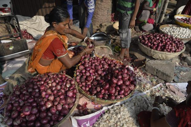 A vegetable seller sorts onions at a roadside market in Siliguri on 28 November 2017. The price of onions have risen sharply in the past few months, quadrupling to as much as Rs65  a kilogram. Photo: AFP