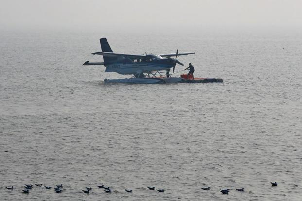 A man anchors an amphibious seaplane from Japan's Setouchi Holdings after it landed in the Arabian Sea as part of a demonstration by SpiceJet in Mumbai on Saturday. Photo: ReutersPhoto: Reuters