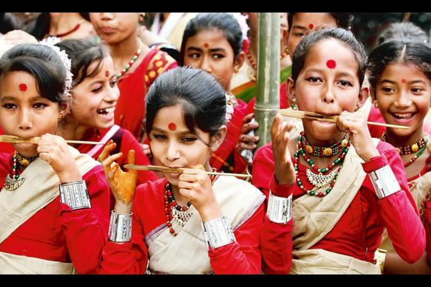 Women and young girls alike would sing songs while making 'pithas', or steamed rice cakes, during Assam's Bihu festival. Photo: Raj K Raj/Hindustan Times