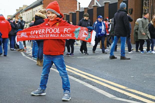 A young Liverpool fan poses outside the stadium at Anfield. Photo: Getty Images
