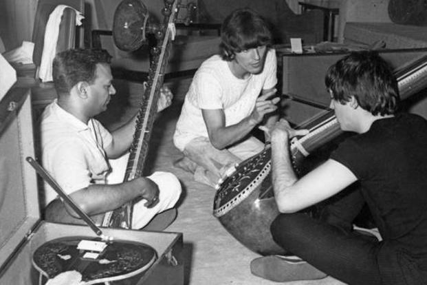 Paul McCartney (right) and George Harrison getting a sitar demonstration in New Delhi on 6 July 1966. Photo: Getty Images