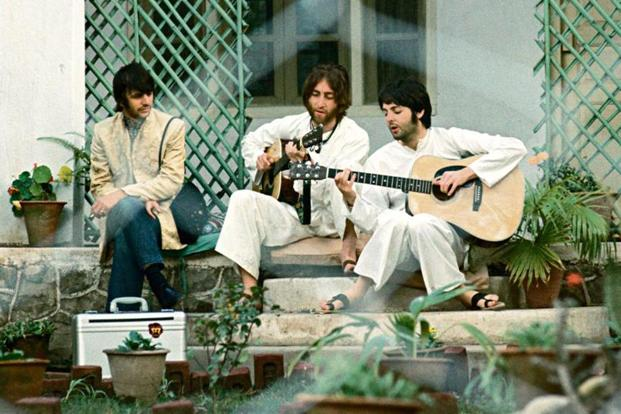 (From left) Ringo Starr looks on as John Lennon and Paul McCartney work on a composition. Photo: Paul Saltzman