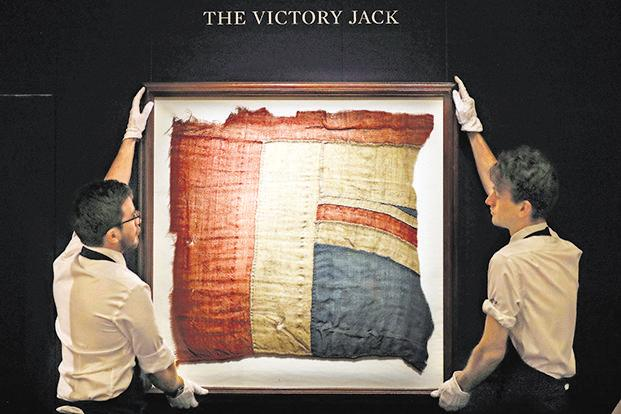 Employees adjust a frame with a fragment of the Union flag, which flew from 'HMS Victory' at the Battle of Trafalgar, at a Sotheby's auction in London last month. Photo: AP