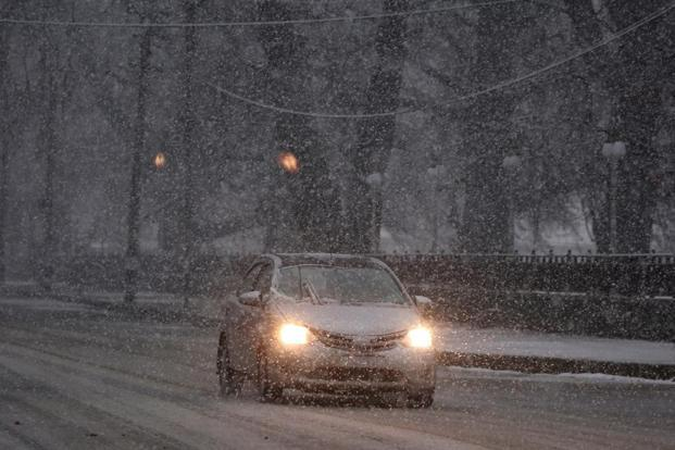 A car moves through a snow-covered road during a snowfall in Srinagar on Monday. Photo: Reuters