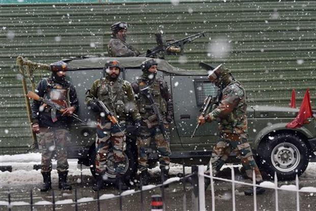 Army personnel take positions during an encounter with the militants, who were taking shelter in a building near a CRPF camp at Karan Nagar in Srinagar on Monday. Photo: PTI