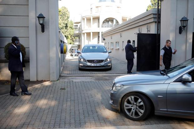 Private security personnel man the gate to the compound of the Gupta family in Johannesburg while cars belonging to the Hawks are stationed outside in Johannesburg, South Africa, on 14 February. Photo: AFP