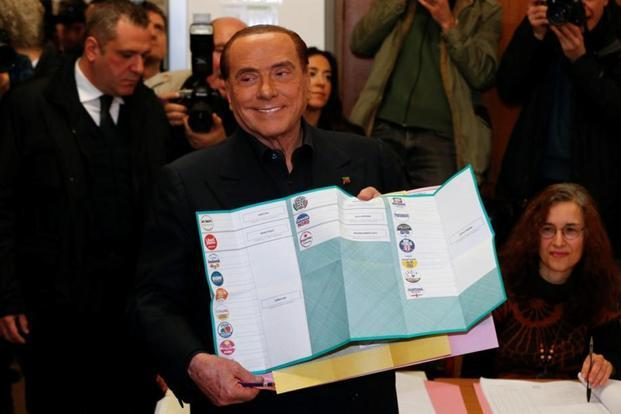 Forza Italia party leader Silvio Berlusconi holds his ballot as he prepares to cast his vote at a polling station in Milan, Italy on Sunday. Photo: Reuters