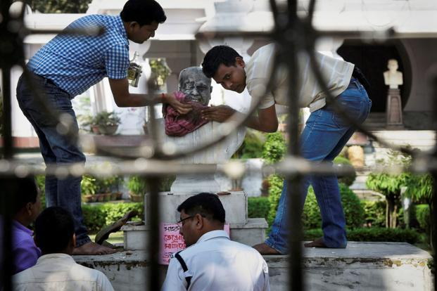 A police official along with a group of people clean the bust of Bharatiya Jana Sangh Bharat Keshri's founder Dr. Syama Prasad Mukherjee after it was vandalized by unknown people at Keoratola Mohasoshan in Kolkata on Wednesday. Photo PTI