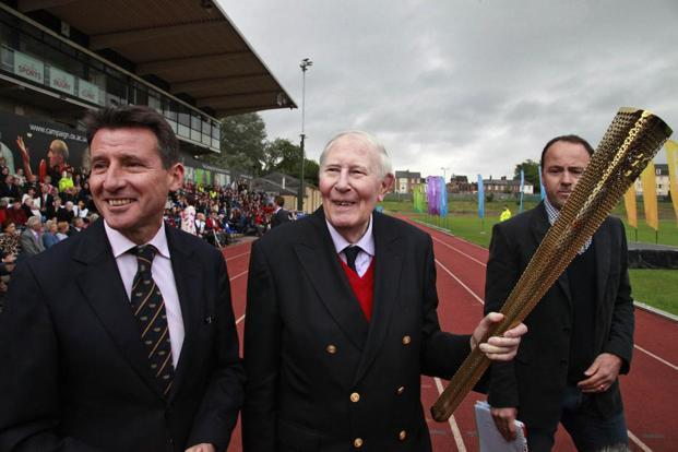 Roger Bannister (centre) passing on the Olympic flame to a torchbearer in Oxford before the 2012 London Games. Photo: AP