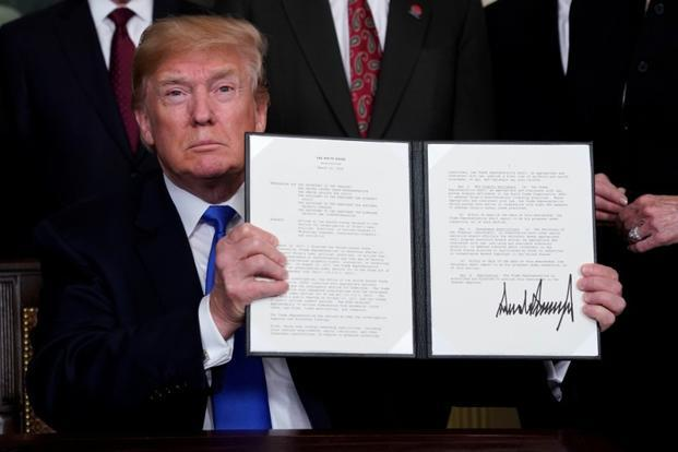 US President Donald Trump holds his signed memorandum on intellectual property tariffs on high-tech goods from China, at the White House in Washington on Thursday. Photo: Reuters