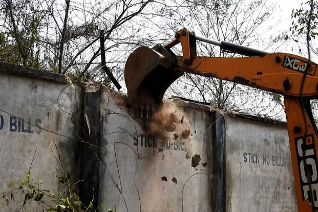 The refinery boundary wall being demolished. Photo Courtesy: Samarjit Sharma