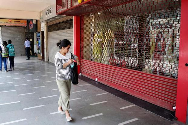 A woman walks past a closed shop in Connaught Place during a strike by traders and workers against the ongoing sealing of unauthorised structures at all the commercial and residential markets in Delhi. Photo: PTI