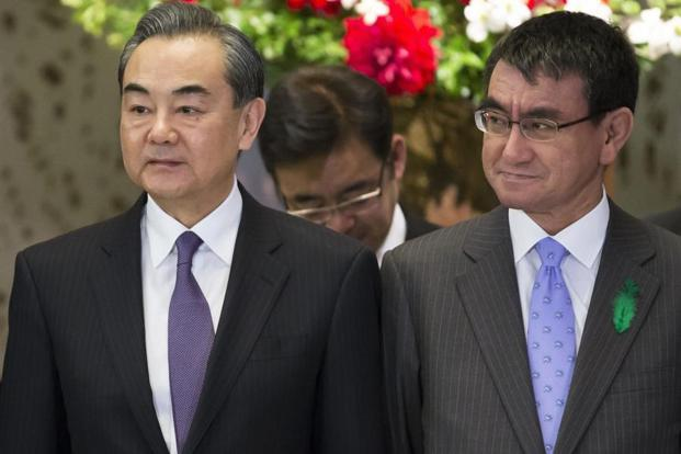 Chinese foreign minister Wang Yi, left, stands with his Japanese counterpart Taro Kono during a photo session before the start of the Japan-China High-Level Economic Dialogue in Tokyo on Monday. Photo: AP