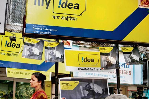 A pedestrian walks past an Idea Cellular retail store in Mumbai. Idea's proposal assumes significance against the backdrop of pending merger with Vodafone India to form the country's largest telecom operator. Photo: Bloomberg