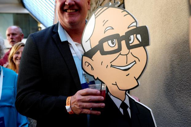 A shareholder holds a drink posing with a cartoon Warren Buffett at the opening cocktail party for the Berkshire Hathaway annual meeting in Omaha, Nebraska on Friday. Photo: Reuters