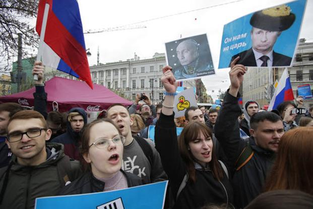 Demonstrators carry posters depicting Russian President Vladimir Putin during a massive protest rally in St.Petersburg, Russia, on Saturday. Photo: AP