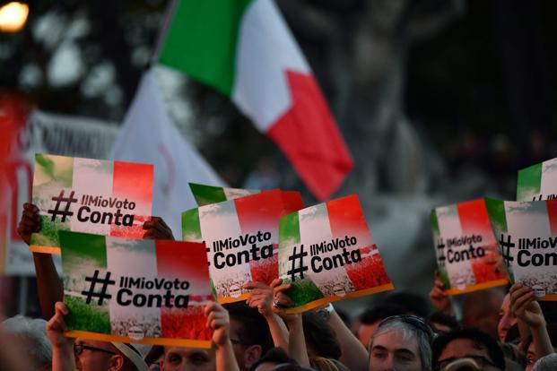 M5S supporters hold banner reading 'My Vote Counts' during a meeting to celebrate the new Italy's government in Rome. Italy's real per capita GDP is currently lower than it was when the euro began in 1998. Photo: AFP