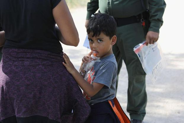 Central American asylum seekers wait as US Border Patrol agents take them into custody on 12 June near McAllen, Texas. Photo: AFP