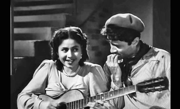 A still from the song 'Tadbeer Se Bigdi Hui Taqdeer Bana Le' ('Baazi', 1951), where Geeta Bali is strumming a guitar.