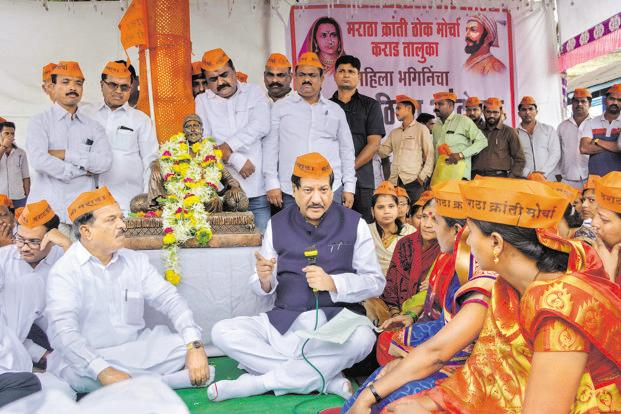 Former Maharashtra chief minister Prithviraj Chavan interacts with Maratha Kranti Morcha activists demanding quota in government jobs and education, in Karad on Monday. Photo: PTI