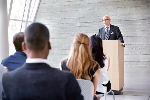Standing behind a podium creates a barrier between you and the audience. Photo: iStock