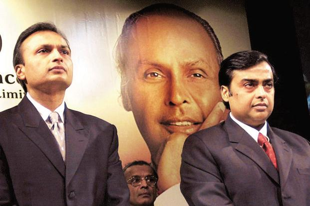 Reliance Industries new chairman Mukesh Ambani and his brother, vice chairman Anil Ambani observe two-minute silence in memory of their late father Dhirubai Ambani at the Annual General Meeting (AGM) in Mumbai on 31 October 2002. Photo: AFP