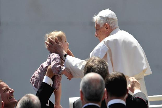 2 May 2012: Pope Benedict XVI kisses a child in St. Peter's square at the Vatican. Born as Joseph Aloisius Ratzinger on 16 April 1927, a native of Bavaria, the Pope has both German and Vatican citizenship. AFP