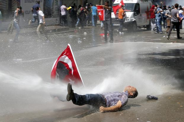 A man is hit by a jet of water during the protests. The controversial redevelopment project aimed at easing congestion around Taksim Square, involves uprooting trees from one of the few green areas left in central Istanbul. Reuters