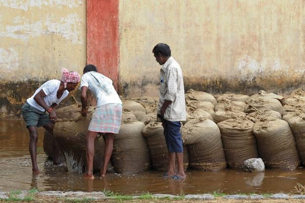 Farmers shift wet bags of rice after overnight rains soaked them at the Agriculture Market Yard, Warangal, near Hyderabad, on 9 May 2014. Post harvest losses of food grains are 20 million tonne, which can be prevented with better storage facilities.<b> AFP </b>